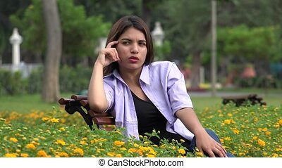Sad Lonely Female Teen Sitting In Park