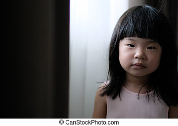 Sad lonely little girl looking at camera