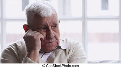 Sad lonely senior man sitting alone at home feeling depressed