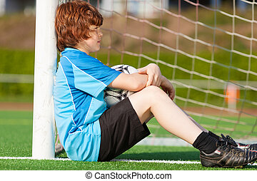 sad looking boy leaning at goal