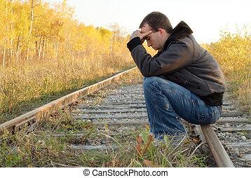 Sad Man - A sad man sitting on a set of railroad tracks ...