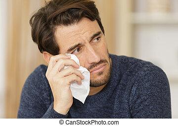 sad man cries at home