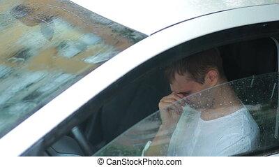 sad man crying in the car. rain on the street