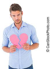 Sad man holding a broken heart