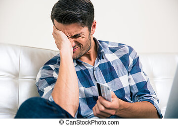 Sad man holding bank card - Portrait of a sad man holding...