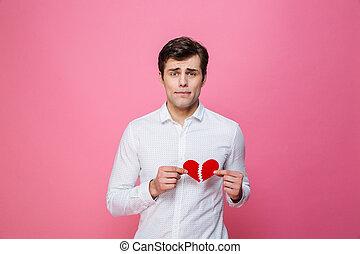 Sad man holding broken heart. Looking camera.