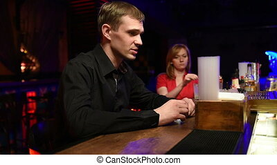 sad man in a bar drinking strong alcohol. He is talking with the bartender