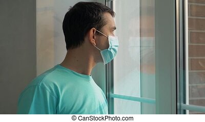 Sad man in a medical mask look at the window