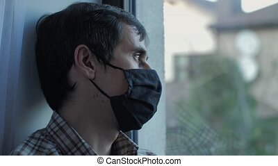Sad man in protective mask look at the window