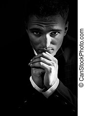 Sad man in the dark praying to God - Sad young man in the ...