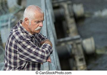 sad man looking at the water
