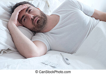 Sad man lying in the bed and feeling bad