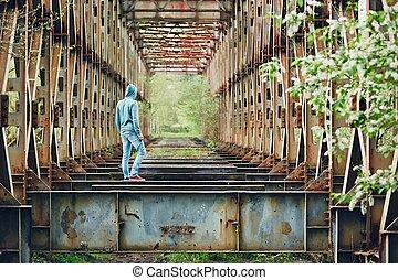 Sad man on the abandoned bridge
