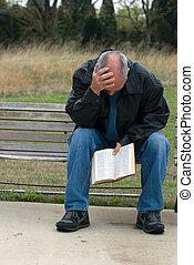 sad man reading bible