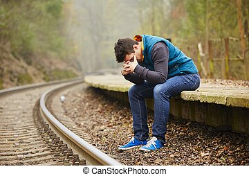 Sad young man at the railway station
