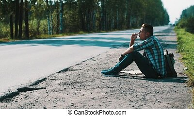 Sad man sit at road in countryside. Hitchhiking. Waiting. Smoking cigarette.