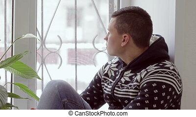 sad man sitting on the window
