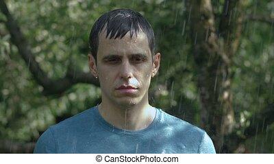 Sad man stands in the rain