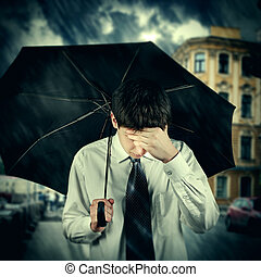 Toned Photo of Sad Young Man with Umbrella under the Rain in the City
