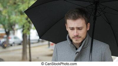 Sad man walking complaining under the rain - Sad man walking...