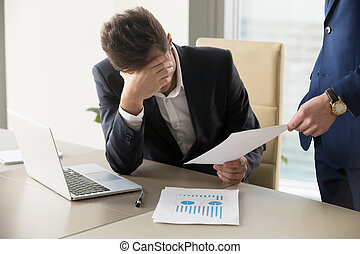 Sad manager getting notice of dismissal, document with bad news