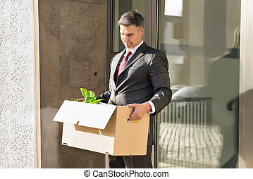 Mature Businessman Moving Out With Cardboard Box From Office