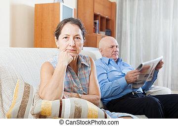 sad mature woman against elderly man with newspaper