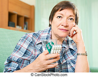 Sad mature woman with pills and glass of water