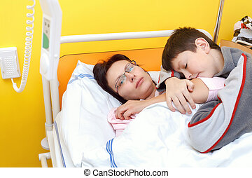 Real people in real situation, sad middle-aged woman lying in hospital with pneumonia, son visit his mother