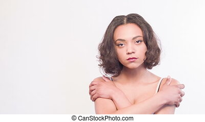 Sad mulatto girl with her hands cross on breast
