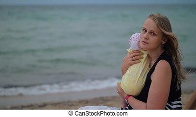 Sad mum with baby near the sea