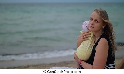 Sad mum with baby near the sea - Young mother holding baby...