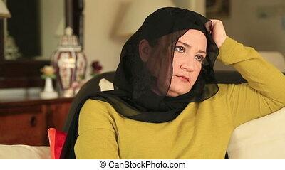 Sad muslim woman sitting on a sofa