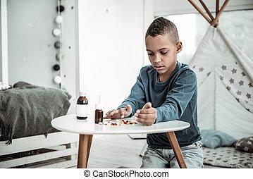 Sad nice boy sitting in his room