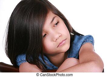 Sad nine year old girl sitting on chair, bored.