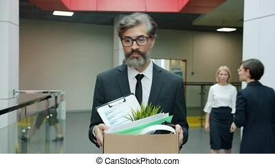 Sad office worker mature bearded man is walking in hallway with carton box leaving work after employment termination. Sacking employees and workplace concept.