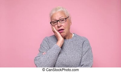 Sad old woman looking at camera showing distrustful look. ...