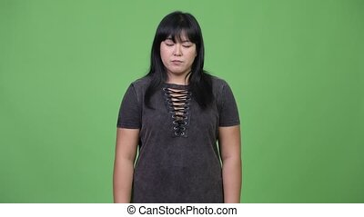 Sad overweight Asian woman giving thumbs down