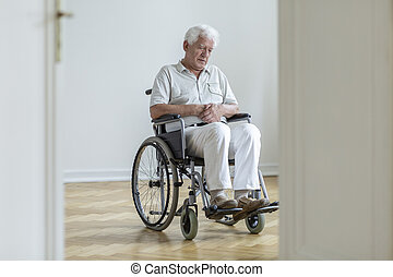 Sad paralyzed senior man in the wheelchair alone at home