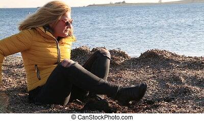 Sad pensive woman on winter sea beach