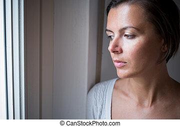Sad pensive woman portrait next to a window