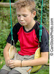 Sad pre-teen boy sitting on a swing