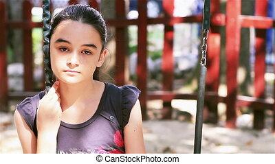 Sad preteen girl sitting on swing in playground
