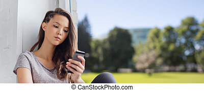 sad pretty teenage girl with smartphone texting - people,...