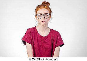 Sad redhead woman with sad eyes looking at camera