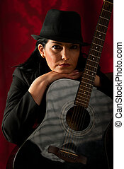 Sad retro woman with guitar in night