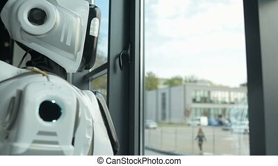 Sad robotic machine touching window while looking outdoors -...