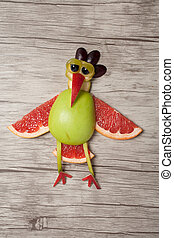 Sad rooster made with fruits on wooden background