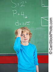 Sad Schoolboy Standing Against Board In Classroom