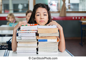 Sad Schoolgirl Resting Chin On Stacked Books At Desk -...